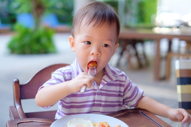 Asian little child sitting in high chair using fork eating Premium Photo