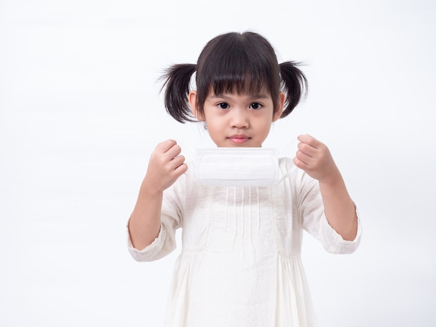 Asian little cute girl 4 years old wearing a hygienic mask to protective spread the corona virus covid-19 cold flu or pollution on white wall. Premium Photo