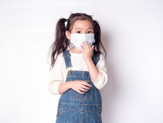Asian little cute girl 6 years old wearing a mask to protective spread the disease Premium Photo