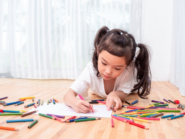 Asian Little Cute Girl Lying On The Floor And Use Color Pencil