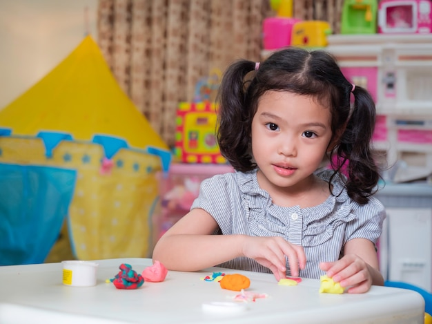 Asian little cute girl playing with play dough on white table at home. Premium Photo