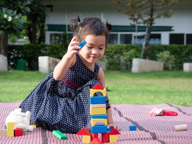 Asian little cute girl playing wooden blocks on mat on the garden. Premium Photo