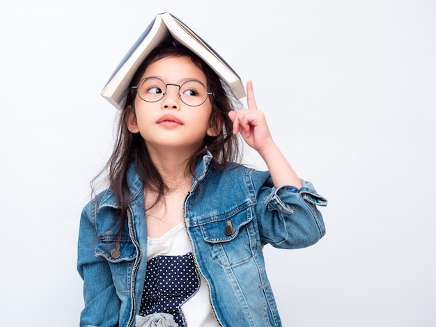 Asian little cute girl wearing glasses with the book on head and pointing finger up. Premium Photo