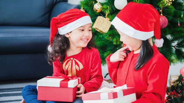 Asian little girl and friend playing and decorating christmas tree in white room at home with gift box together.smiling face and happy to celebrate festivel new year holiday with family. Premium Photo