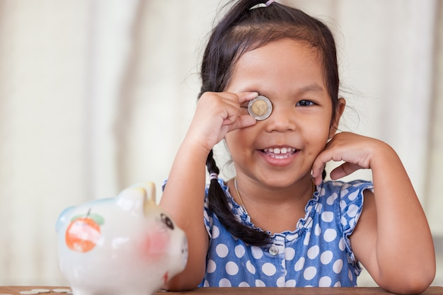 Asian little girl having fun playing with coin Premium Photo