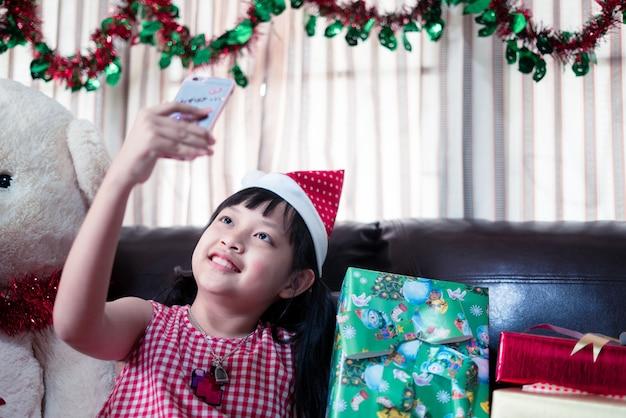 クリスマスのサンタクロースの帽子をかぶったアジアの少女がビデオ通話のためにスマートフォンを見る Premium写真