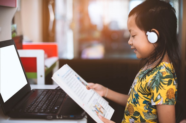 Asian little girl reading a book with search data by notebook. Premium Photo