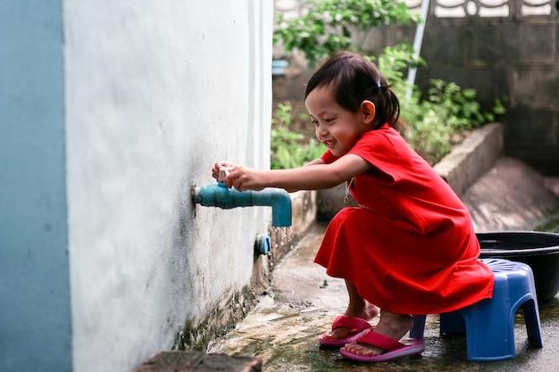 손을 씻고 집에서 가까운 아시아 소녀 프리미엄 사진