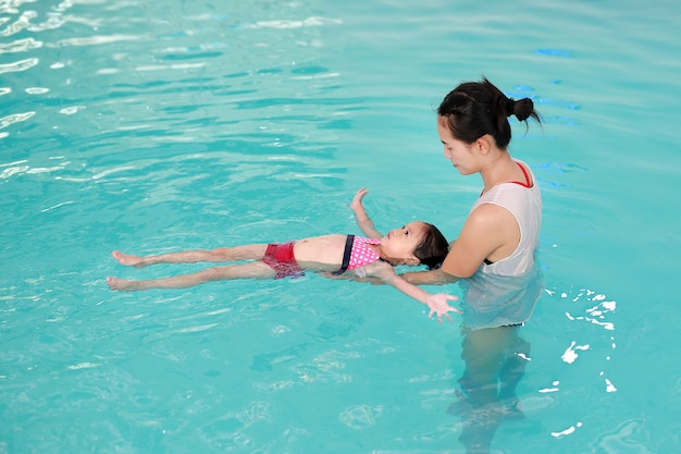 Asian little girl with mother swimming at water pool Premium Photo