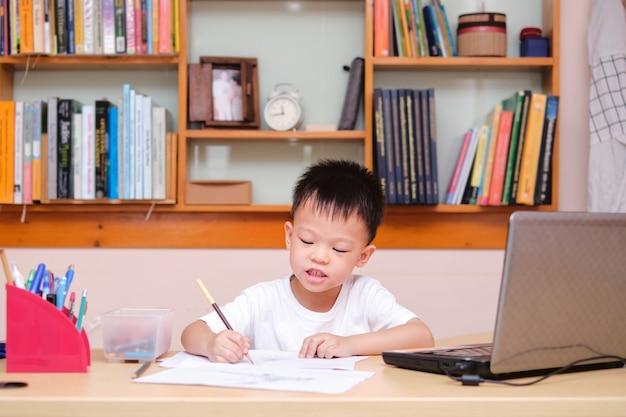 Азиатский чертеж маленького ребенка во время его онлайн урока дома, дистанционное обучение, концепция homeschooling Premium Фотографии