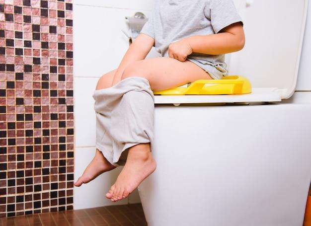 Asian little kid sitting on a kid bathroom accessory toilet Premium Photo