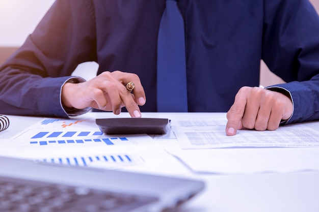 Asian male accountants or bankers perform calculations. Premium Photo