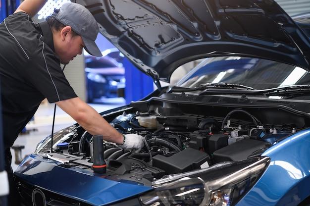Asian male auto mechanic examine car engine breakdown problem in front of automotive Premium Photo