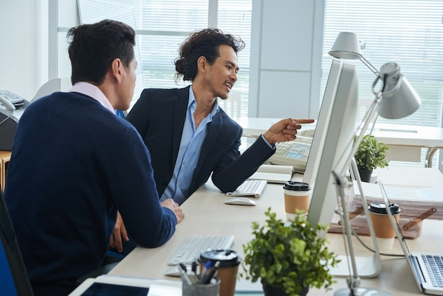 Asian male colleagues looking at computer screen together in office Free Photo