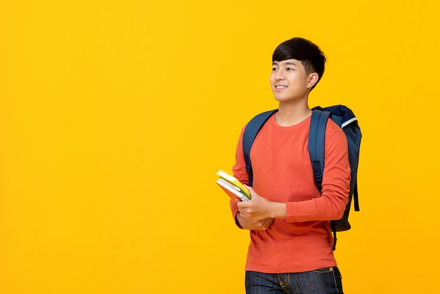 Asian male college student with backpack holding books Premium Photo