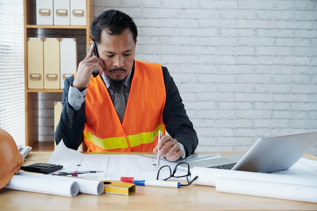 Asian male construction firm executive sitting in office and talking on phone Free Photo
