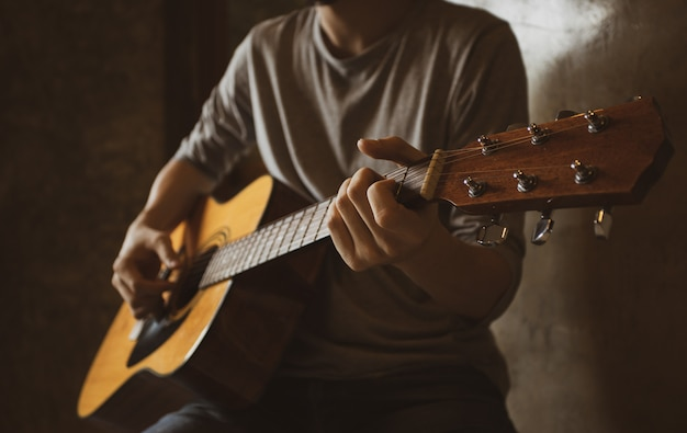 Asian male musician playing acoustic guitar solo finger style picking in room corner. Premium Photo