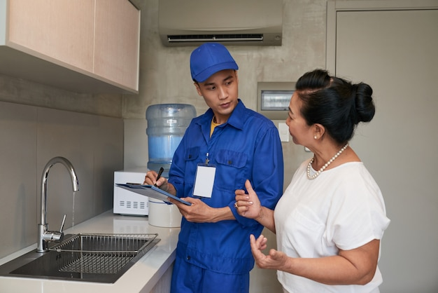 Asian male plumber in uniform talking to senior female homeowner in kitchen Free Photo