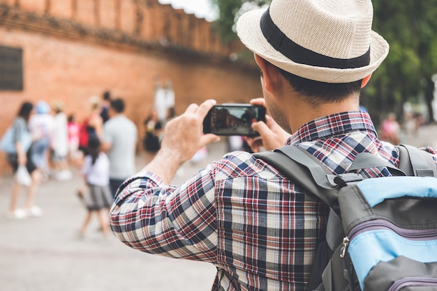 Asian male tourist backpacker taking photo with smartphone at tha phae gate, one of the ancient famous landmark of the city in chiang mai thailand Premium Photo