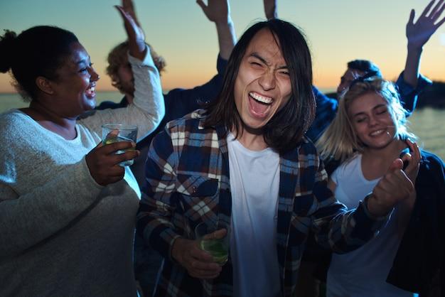 Asian man among dancing friends Free Photo