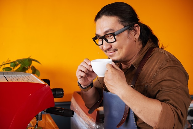 Asian man in apron standing next to espresso machine, holding cup and smelling coffee Free Photo