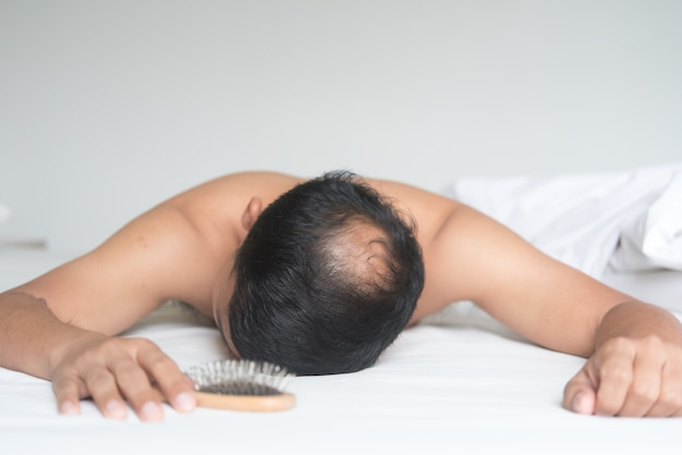 Азиатский мужчина обеспокоен проблемой выпадения волос на кровати дома. Premium Фотографии