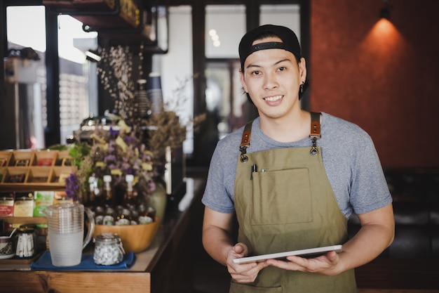 Asian man barista holding tablet for checking order from customer on coffee cafe. Free Photo