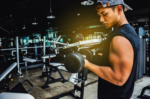 Asian man bodybuilder with dumbbell weights power handsome