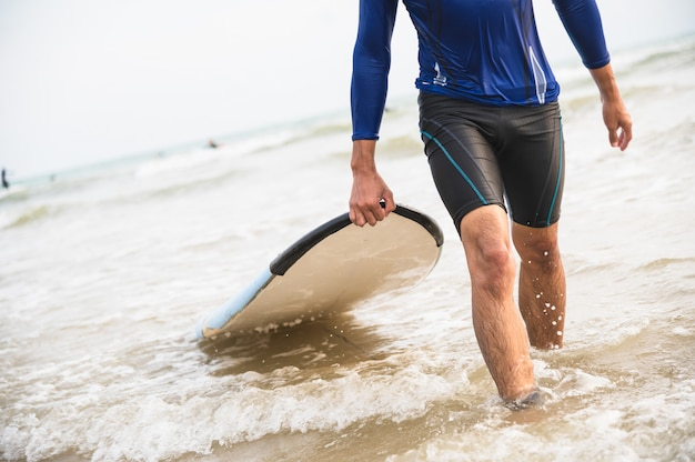 Asian man carry surfboard at the beach Premium Photo