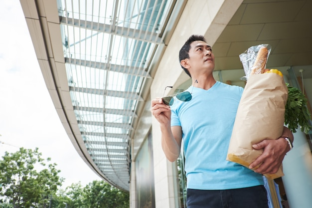 Asian man carrying bag with groceries through shopping mall and looking around Free Photo
