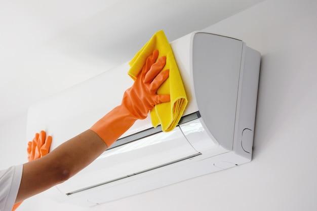 マイクロファイバーの布でエアコンを掃除するアジア人男性 Premium写真