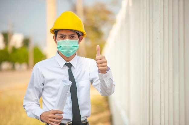 Asian man engineer use face mask yellow hard hat holding blueprint inspection construction building estate Premium Photo