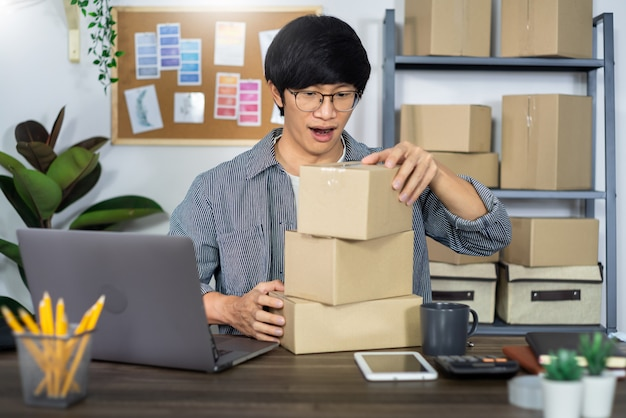 Asian man entrepreneur startup small business entrepreneur sme freelance man working with box to online marketing packaging and delivery scene at home office, onlinebusiness seller concept. Premium Photo