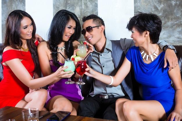 Asian man flirting with women in nightclub Premium Photo