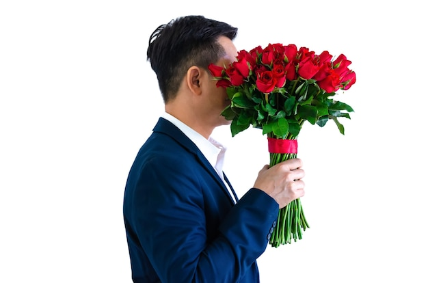 Азиатский мужчина держит букет красных роз на день святого валентина концепции. Premium Фотографии