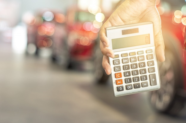 Asian Man Holding Calculator For Business Finance On Car Showroom
