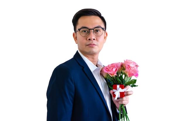 Азиатский мужчина держит розовые розы и подарочную коробку для концепции дня святого валентина. Premium Фотографии