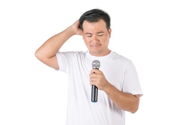 Азиатский мужчина держит беспроводной микрофон и забыл, что сказать Premium Фотографии