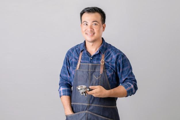 コーヒー工作機械を保持しているバリスタの制服を着たアジア人 Premium写真