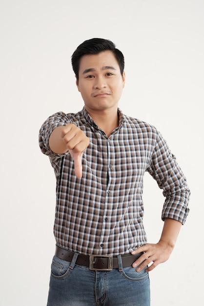 Азиатский мужчина в клетчатой рубашке и джинсах, стоя в студии с его пальца вниз Бесплатные Фотографии
