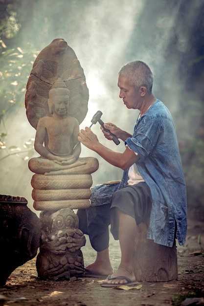 Asian man is carved stone into a buddha image ayutthaya thailand Premium Photo