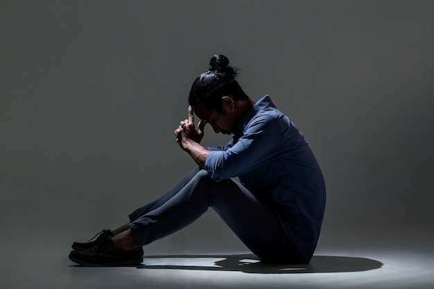 An asian man is suffering from depression in darkness. Premium Photo