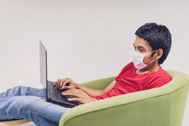 Азиатский мужчина работает из дома во время coronavirus или covid-19. носить защитную маску для защиты от коронавируса, работать дома и пользоваться ноутбуком. работа из дома, оставайся дома. социальное дистанцирование. Premium Фотографии