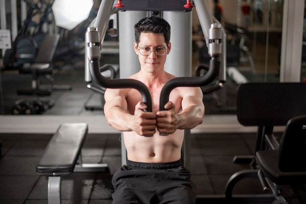 Asian man is working out  in fitness gym Premium Photo