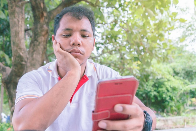 Asian man looking smart phone.he feel bored time. Premium Photo