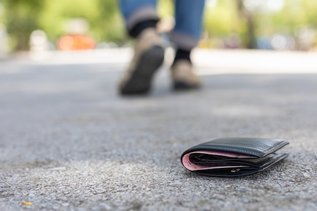 Asian man lose black wallet on the road in tourist attraction Premium Photo