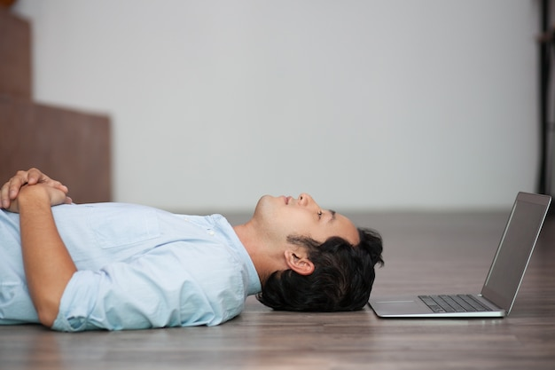 Asian man lying on floor at his laptop