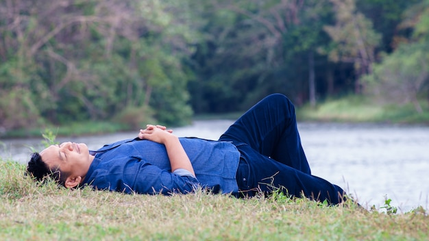 Asian man lying on the ground in the midst of nature with happy and comfort. Premium Photo