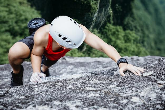 Asian man rock climber in black pants climbing on the cliff. Premium Photo