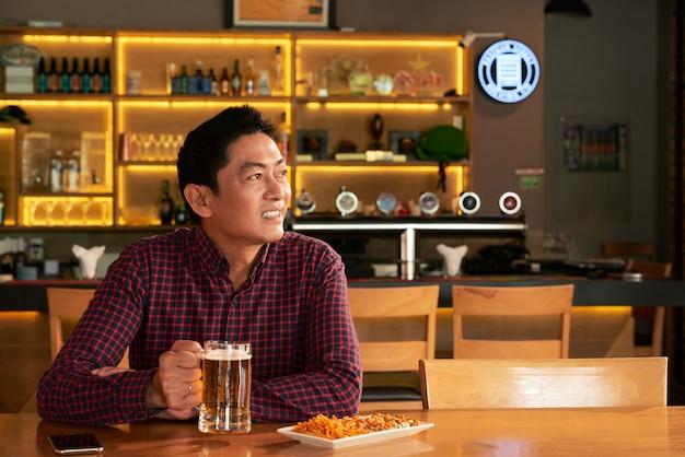Азиатский мужчина сидит в пабе с кружкой пива и закусок и смотрит на что-то Бесплатные Фотографии